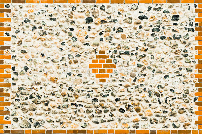 Flint stone wall. A renovated flint stone wall with modern red bricks royalty free stock photography