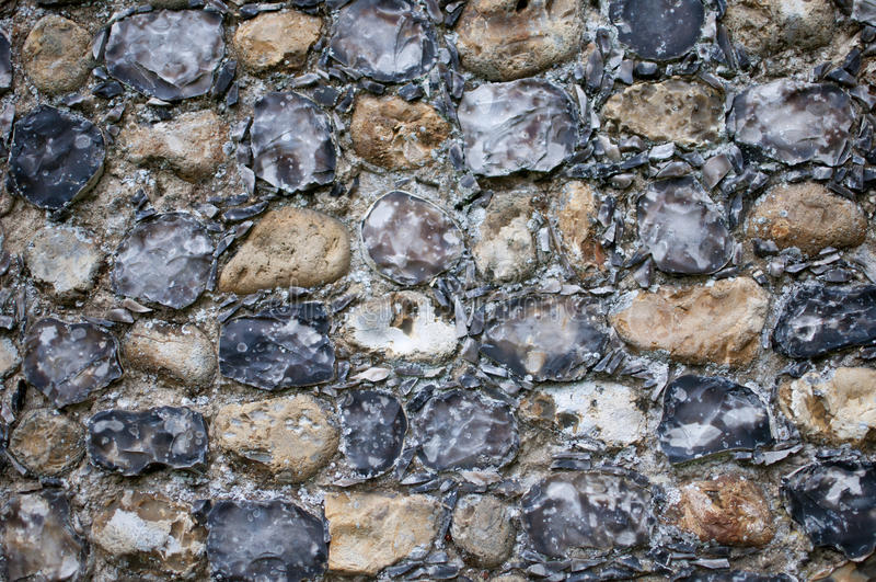 Flint wall from Norfolk, England. Detail of an ancient flint wall from a church in England.The flints are knapped (split) and mortered close together royalty free stock photo