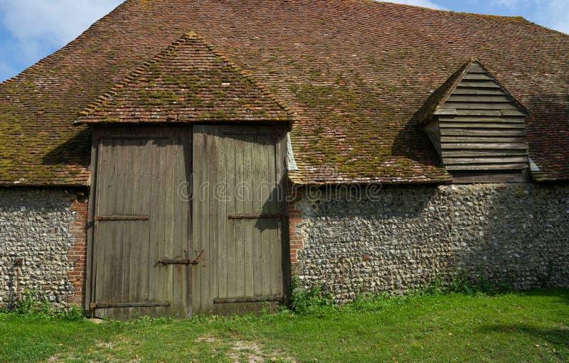 Flinta byggd ladugård med dubbla dörrar för enormt trä royaltyfria foton
