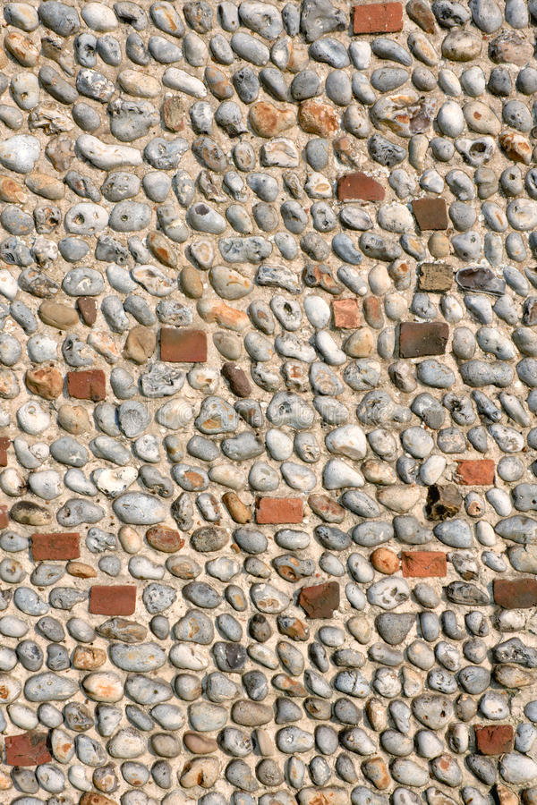 Stone Wall Background. Detail of a church wall made of flint-stone pebbles and red brick. Stalham, Norfolk, England royalty free stock photo