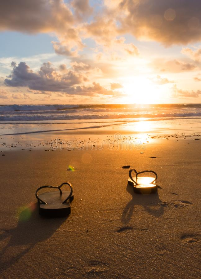 Flip floops at the beach. A pair of flip floops at a sunrinse on the beach royalty free stock photography