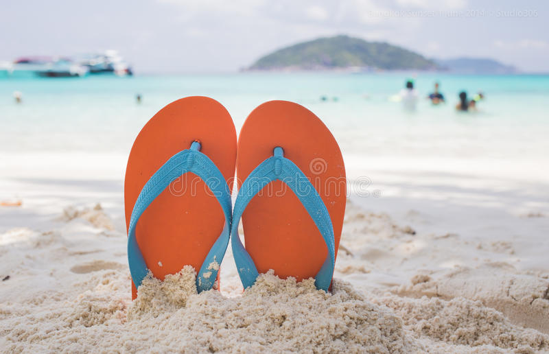 Flip-flop on the beach. Orange flip-flop on the white sand beach royalty free stock photography