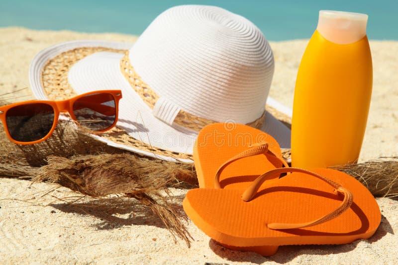 Flip-flop bianchi del cappello e lozione d'abbronzatura immagini stock