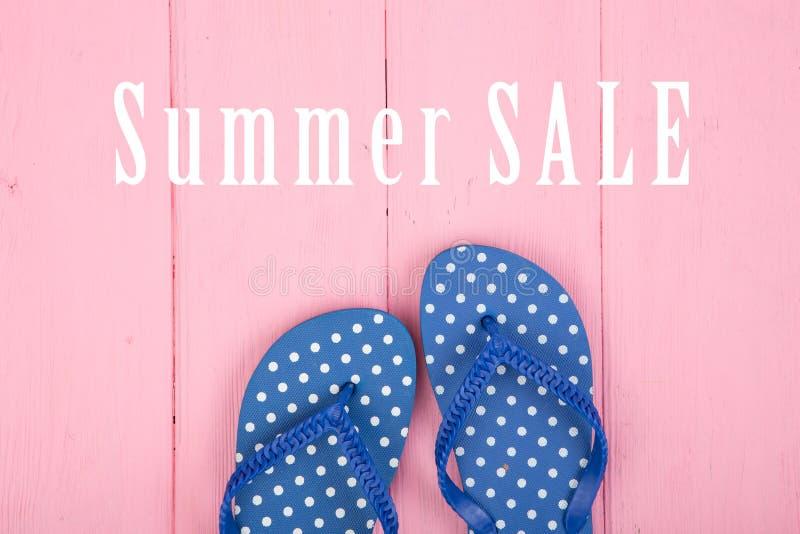 Flip-flop blu in pois e vendita di estate del testo sul rosa fotografie stock