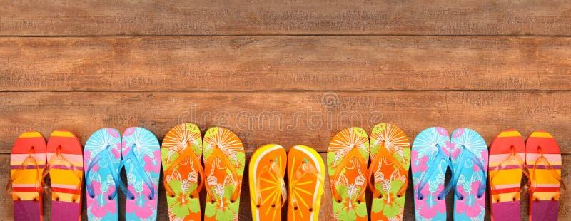 Flip-flop brillantemente colorati su legno immagine stock