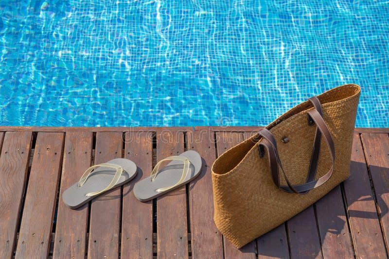 Flip-flop e borsa della spiaggia sulla piattaforma di legno accanto alla piscina immagine stock libera da diritti