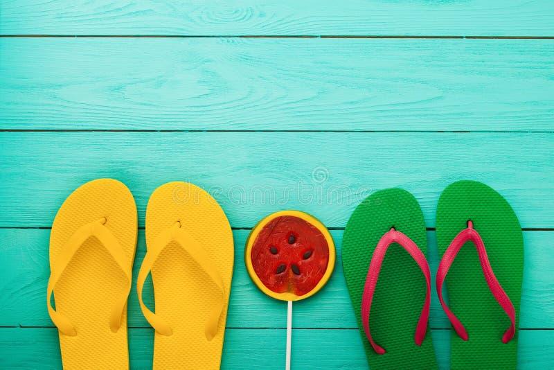 Flip-flop e caramella su fondo di legno blu Vista superiore Derisione su Copi lo spazio Festa della spiaggia di estate fotografie stock