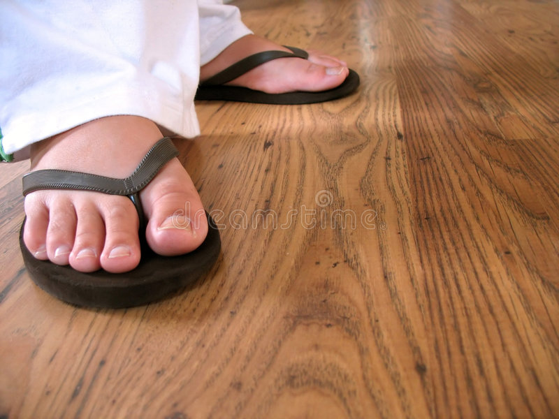 Flip flop feet. A closeup of a woman's feet wearing some black flip flops stock photos