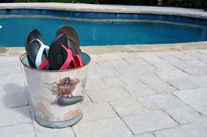 Flip flop fun. Bucket of flip flops in a bucket with a mermaid on it, sitting by a pool ready for anyone to put on royalty free stock images