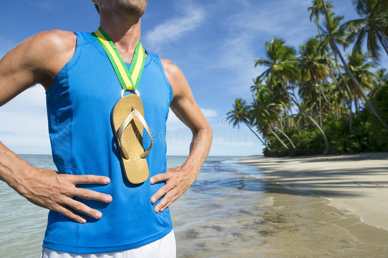 Flip Flop Gold Medal Brazilian Athlete Beach. First place Brazilian athlete standing with flip flop gold medal on empty beach stock image