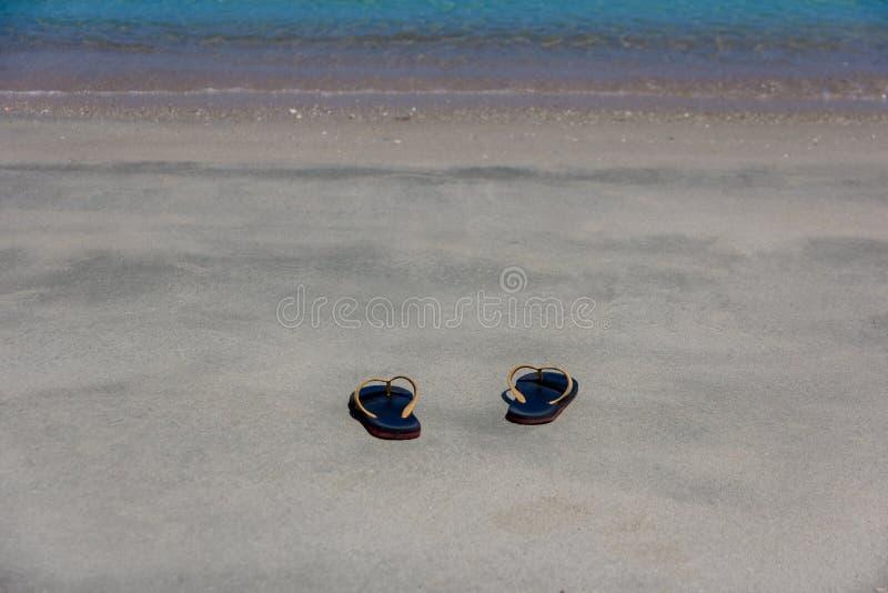 Flip-flop nero su una spiaggia dell'oceano, su una vacanza estiva e su un concetto sabbiosi di vacanza fotografie stock