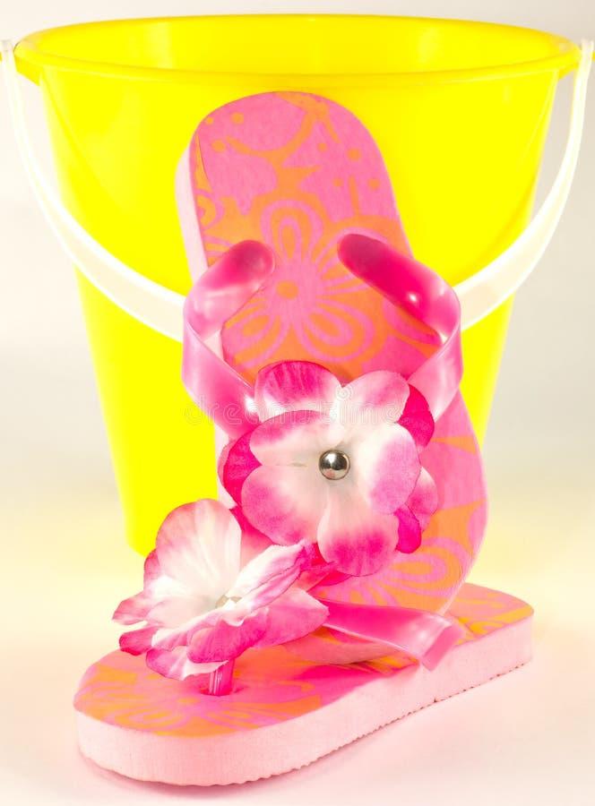 Flip-flop rosa e secchio giallo sabbia fotografia stock
