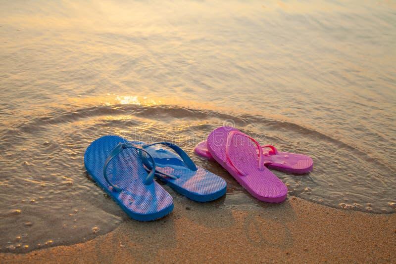 Flip flop sandals on the beach. Romantic beach scene. Female and male flip flop sandals on the beach stock photo