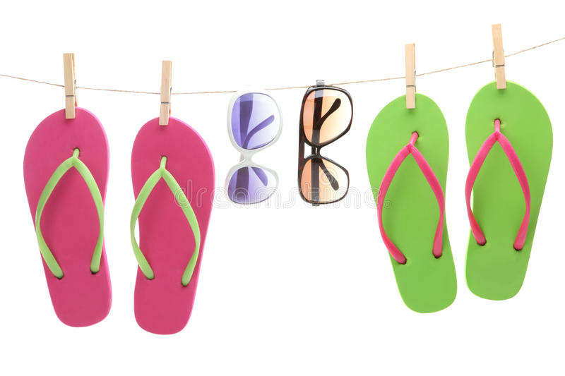 Flip-flop sandles and sunglasses hanging by clips. From a clothes line royalty free stock images