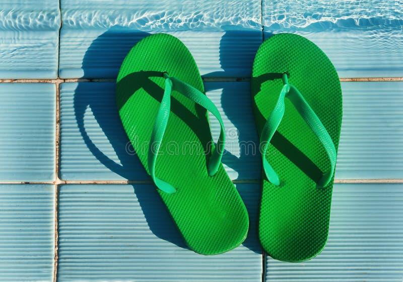 Flip-flop verdi che stanno sullo stagno blu delle mattonelle fotografie stock libere da diritti