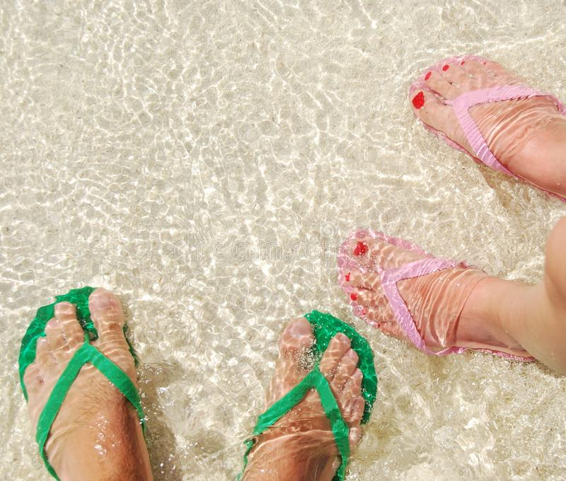 Flip flops. Close up of feet and flip flops on a translucent ocean water royalty free stock images