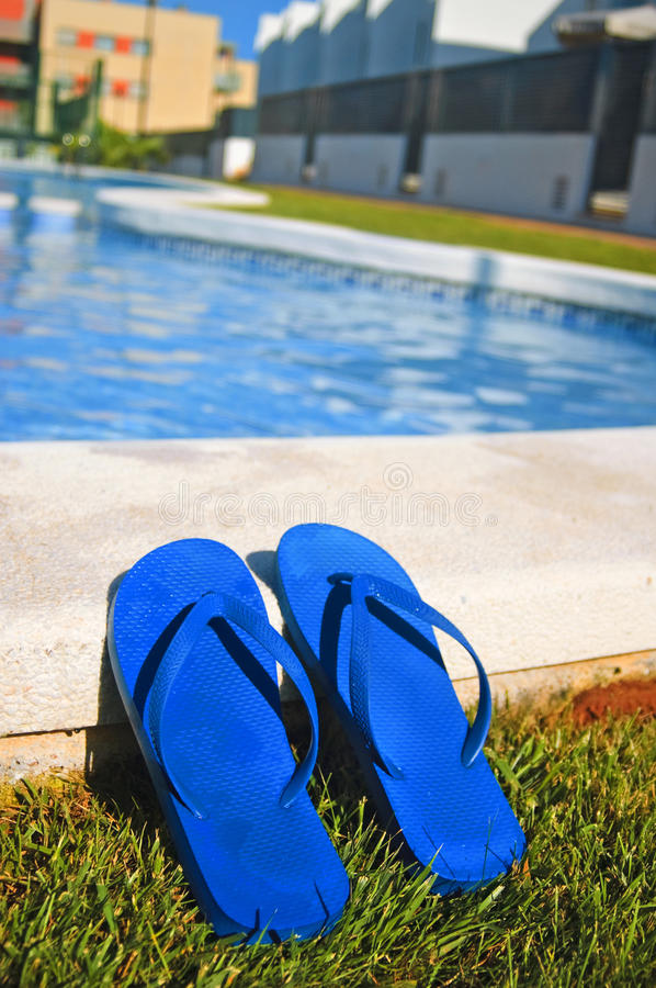 Flip-flops. A pair of flip-flops on a swimming pool stock photos