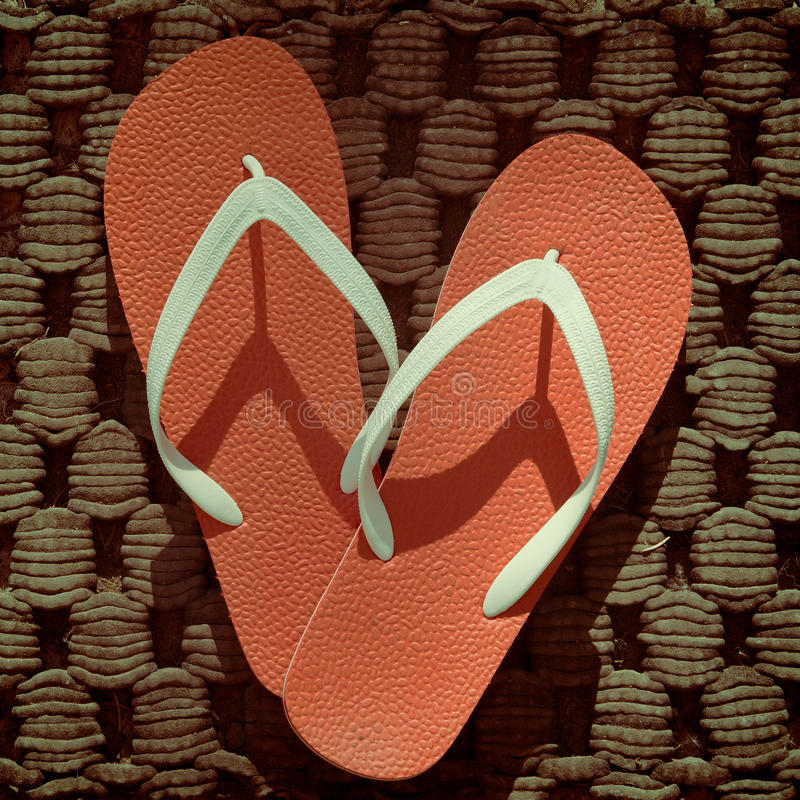 Flip Flops. Red and white flip flops placed on an old doormat stock images