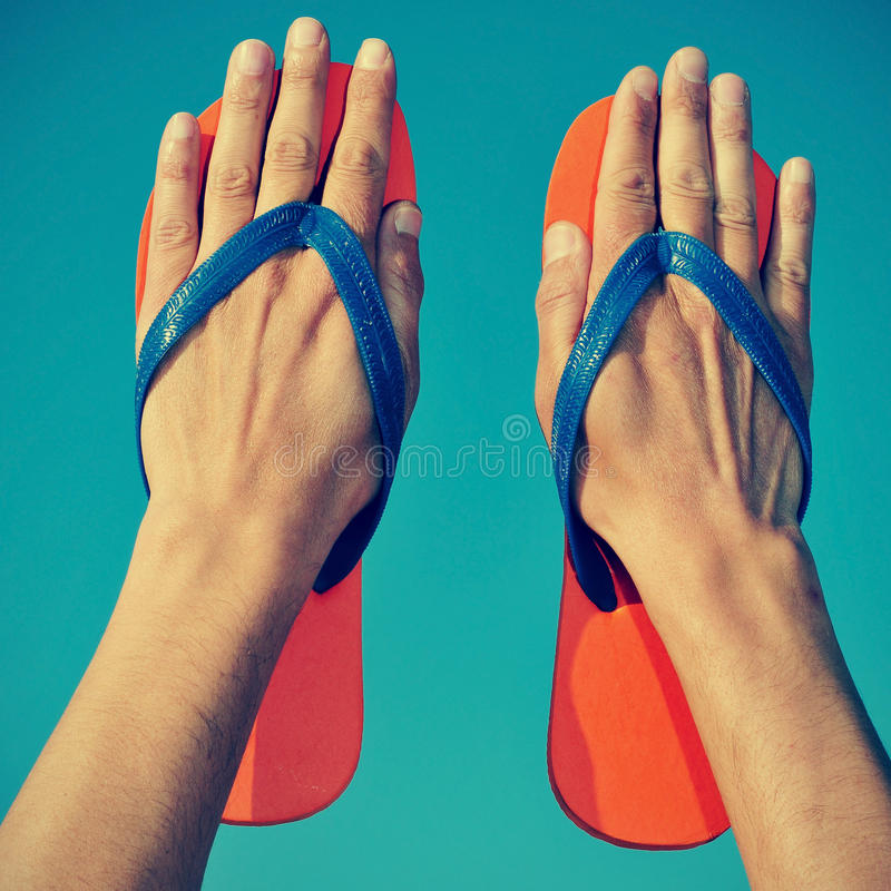 Flip-flops. Someone wearing flip-flops on his hands over the blue sky royalty free stock photo