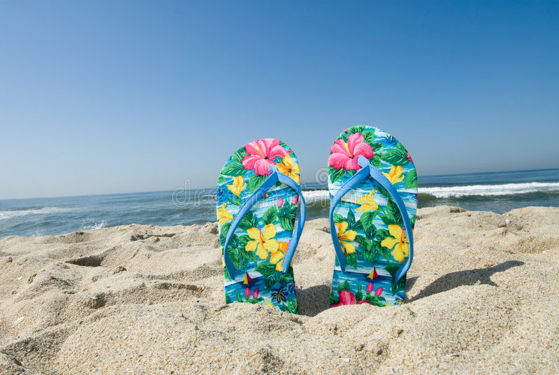 Flip flops. A pair of flip flops stuck in the sand by a beachgoer royalty free stock image