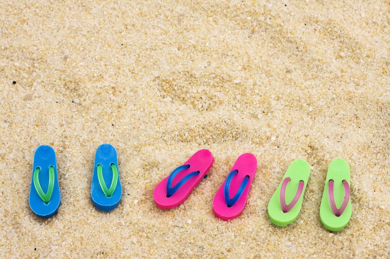 Flip Flops. Colored Flip flops on sand ? beach background royalty free stock photos