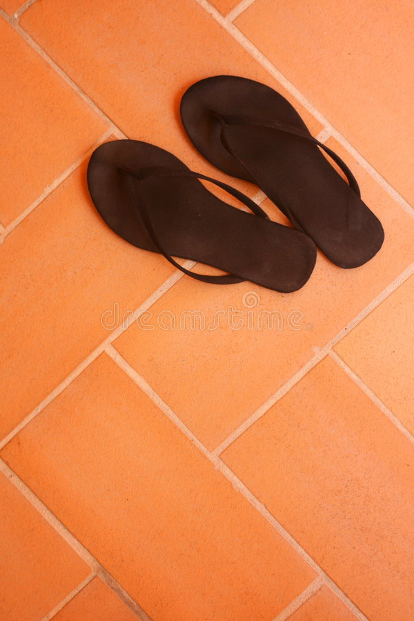 Flip-flops. Flip flops over a tiled orange floor royalty free stock photos