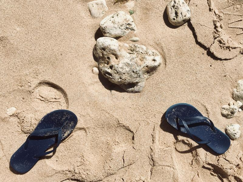 Flip-flops azuis em Sandy Beach fotografia de stock