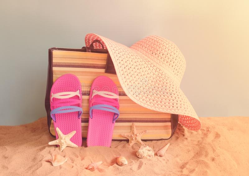 Flip flops, bag, summer hat and seashells on sand beach on blue backdrop. stock photography