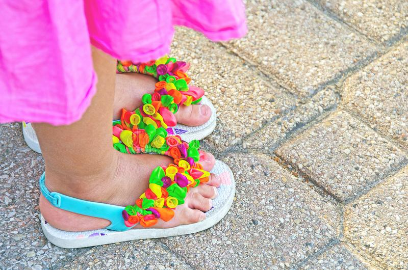 Flip-flops with balloon decoration. Close up of little girl in pink dress wearing sandals with balloon decoration royalty free stock photo