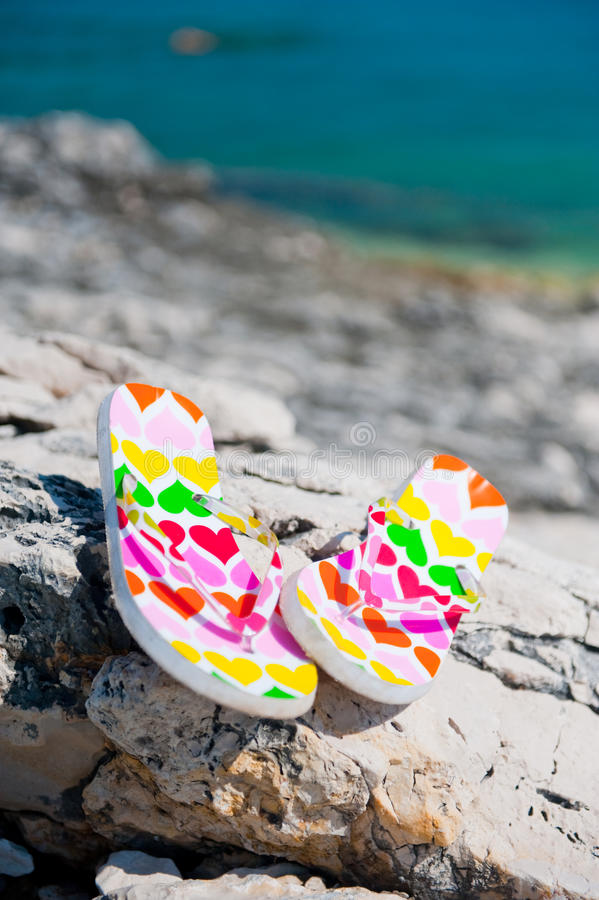 Flip-flops on the beach. Shoes laying on the rocks, Croatia stock photo