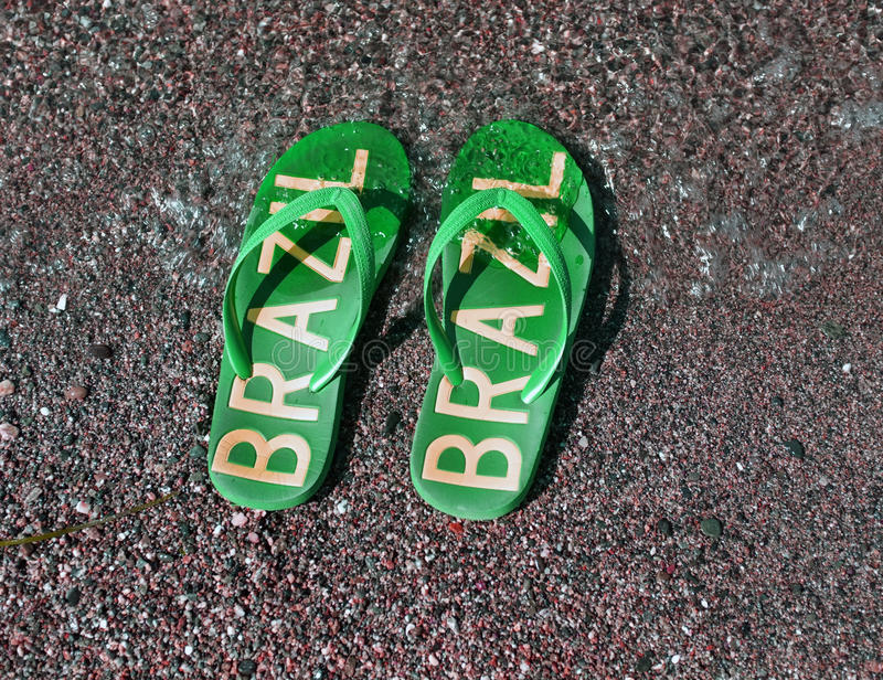 Flip flops on the beach. A pair of green flip flops with Brazil text on it lays on a beach stock photo