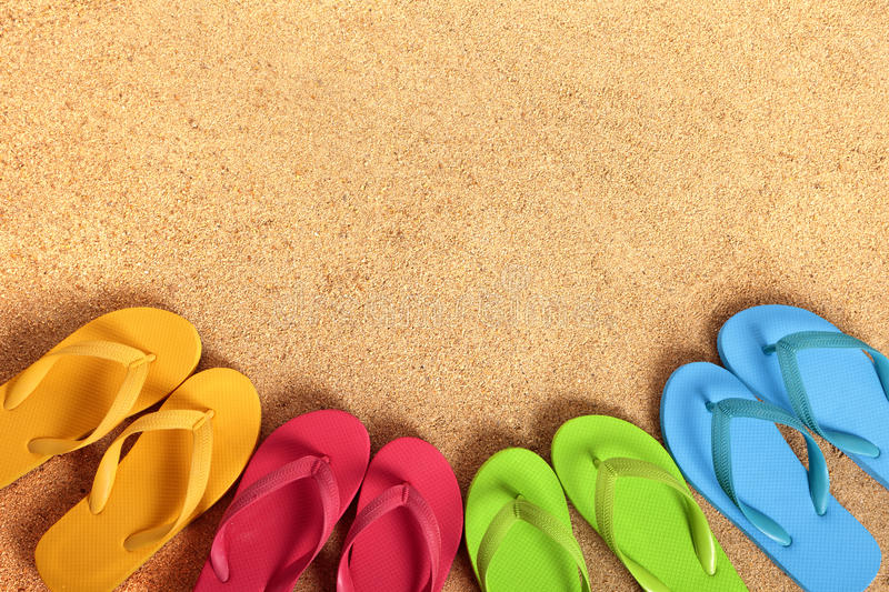Flip flops on beach summer background, sand copy space. Row of flip flops on a sandy beach background. Copy space stock image