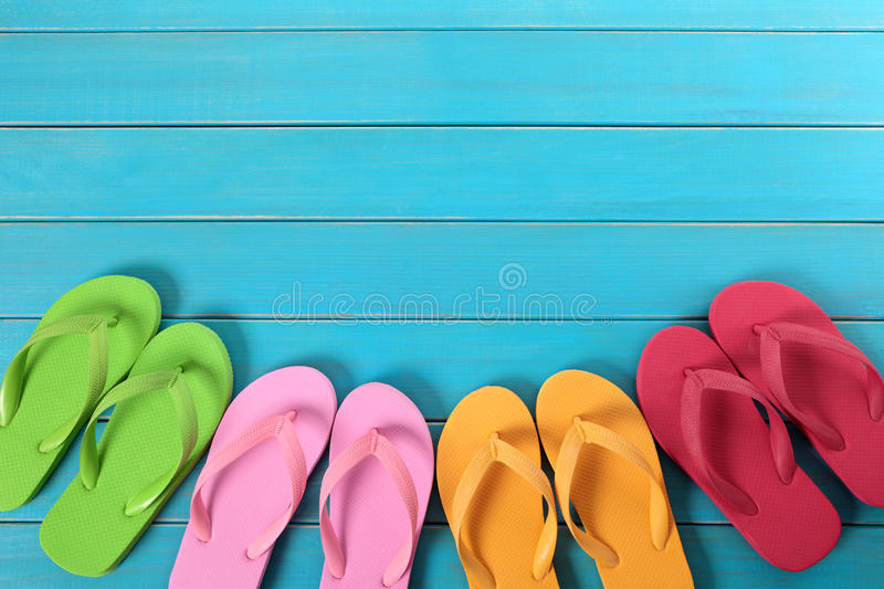 Flip flops. Row of colorful flip flops on old weathered blue painted beach decking. Space for copy royalty free stock photo