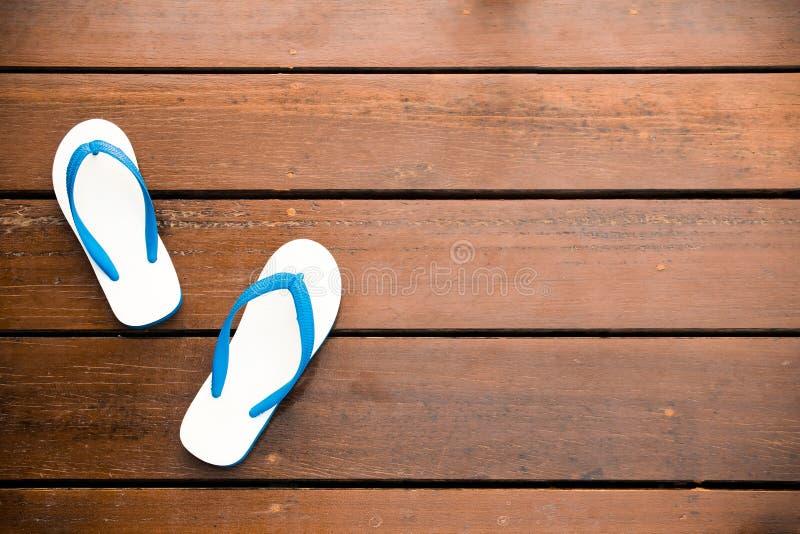 Flip-flops brancos em um fundo de madeira imagens de stock royalty free