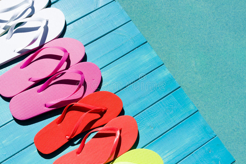 Flip flops. Colorful flip flops by a swimming pool royalty free stock image