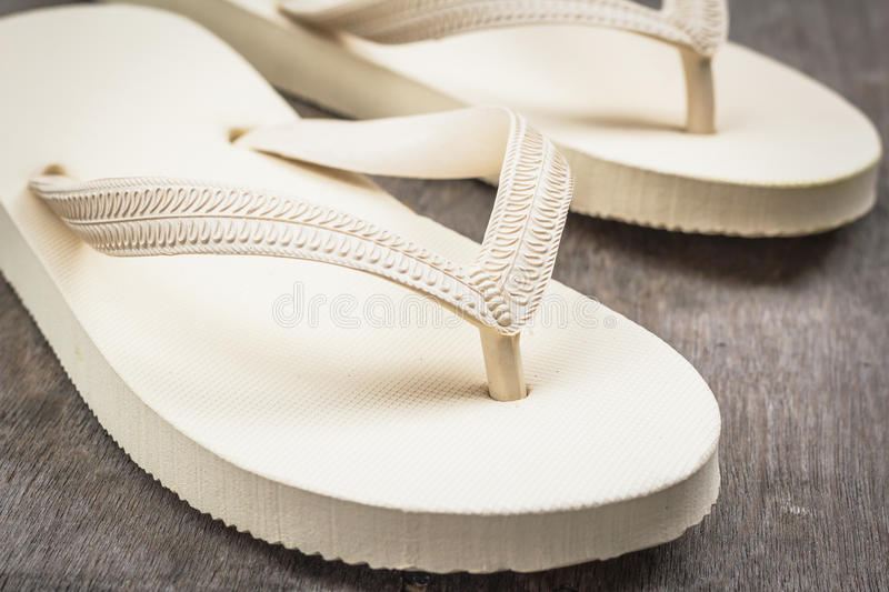 Flip-flops cream color. Flip-flops cream color on a wooden background stock photography