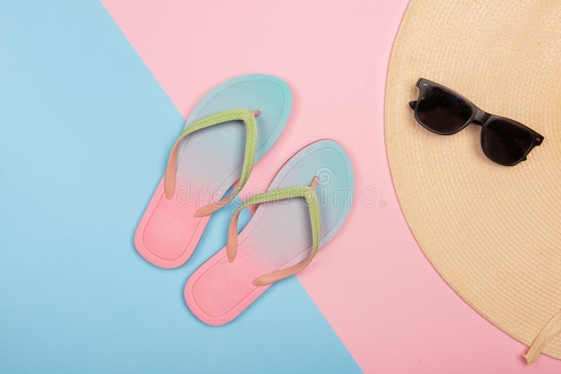 Flip-flops de praia, óculos escuros e chapéu de sol em fundo pastel rosa e azul, vista superior Conceito de Verão com cópia imagens de stock