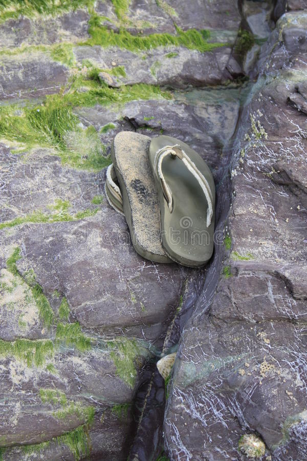 Flip flops discarded on a beach rock stock image