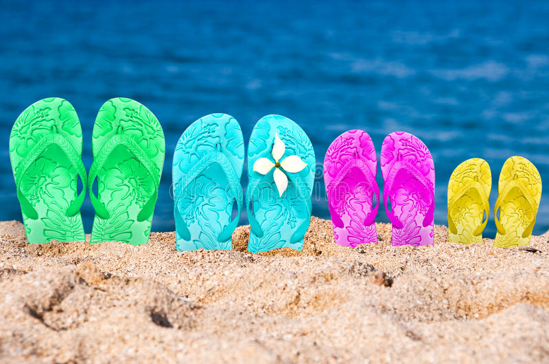Flip flops of a family of four in the sand. Of a beach royalty free stock images
