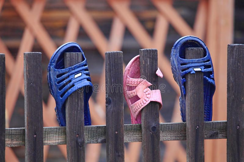 Flip flops on the fence stock images