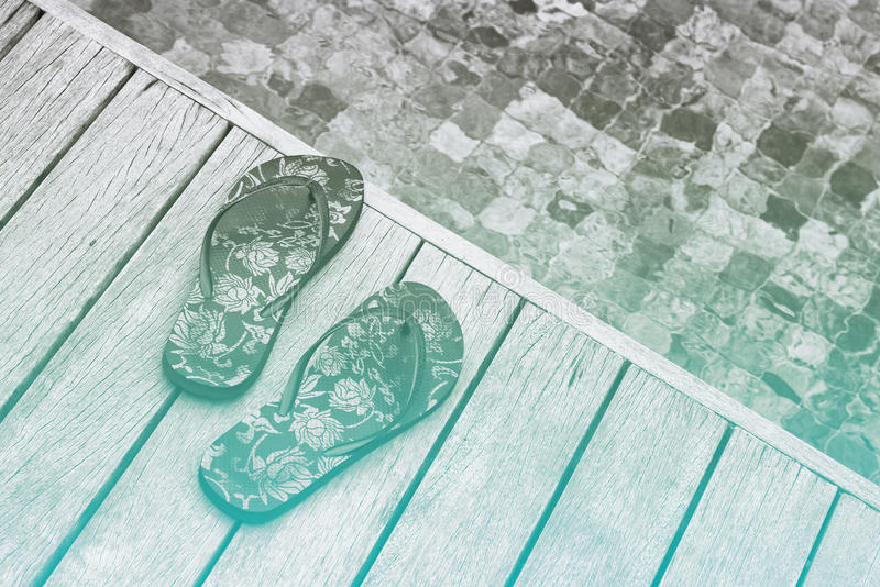 Flip Flops floral en el borde de madera de la piscina fotografía de archivo