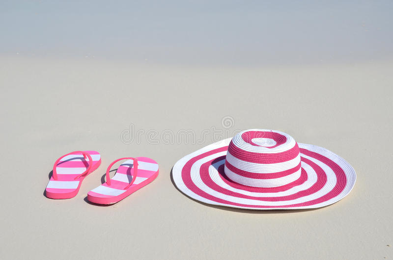 Flip-flops and hat. On the beach royalty free stock photo
