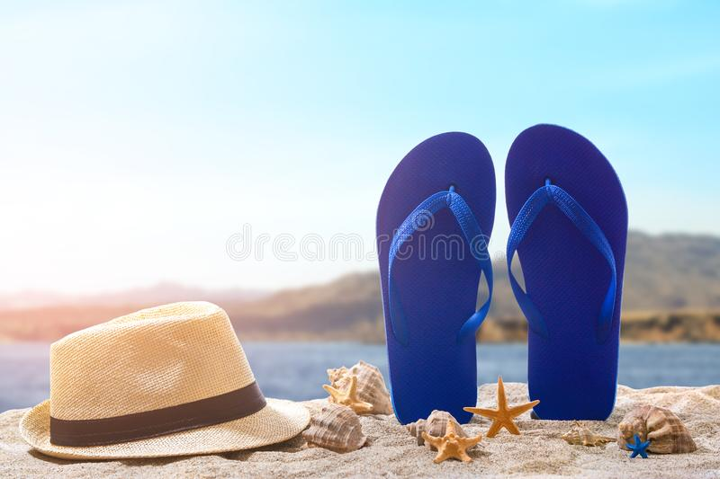 Flip-flops with hat and seashells on sand beach at resort stock images