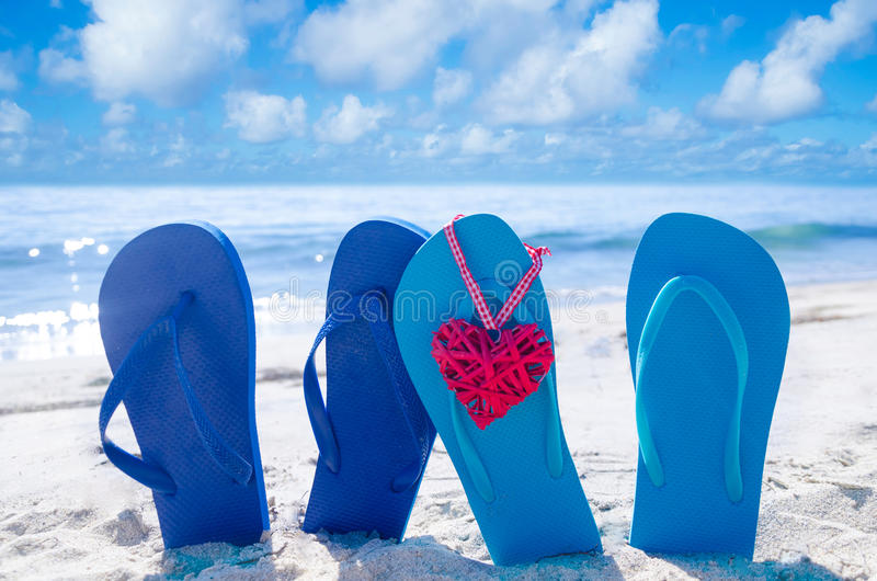 Flip flops with heart on the beach. Flip flops with heart shape on the sandy beach by the ocean royalty free stock image