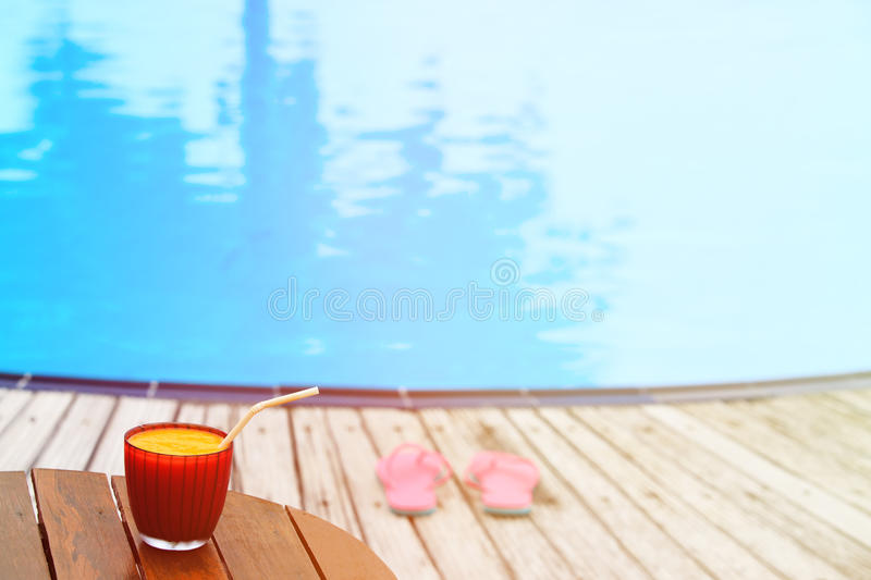 Flip flops and juice on tropical beach. Resort stock images