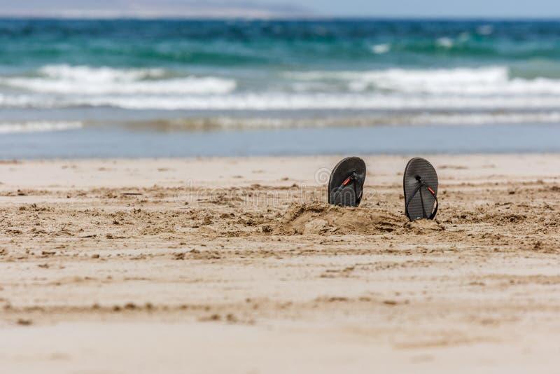 Flip-flops na areia com mar azul e em ondas no fundo La Graciosa, Lanzarote, Ilhas Canárias, Espanha foto de stock royalty free