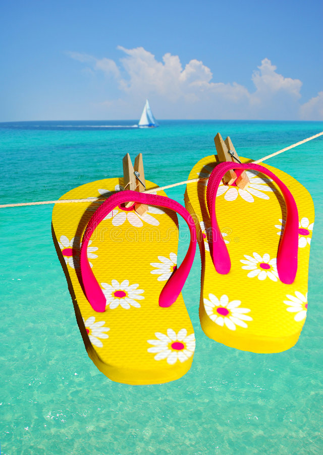 Flip flops at ocean. With sailboat in distance stock photos