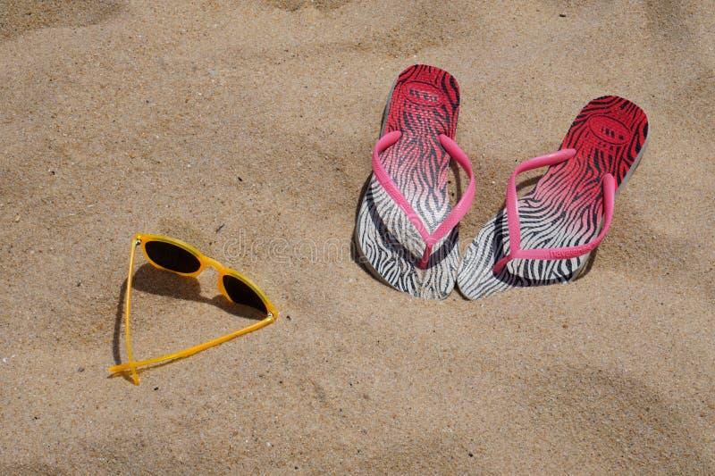 Flip Flops och solglasögon på en sandig strand arkivfoto