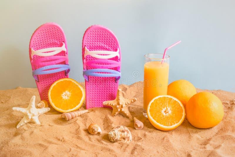 Flip flops, orange juice, oranges, starfishes and seashells on sand beach on blue backdrop. stock photo