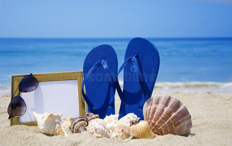 Flip-flops with photoframe and seashells on sandy beach stock photos